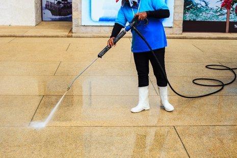 una donna pulisce le fughe del pavimento nell'atrio di un condominio