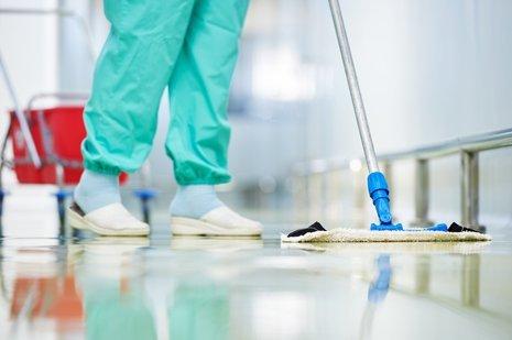 un operaio in divisa sanitaria pulisce il pavimento