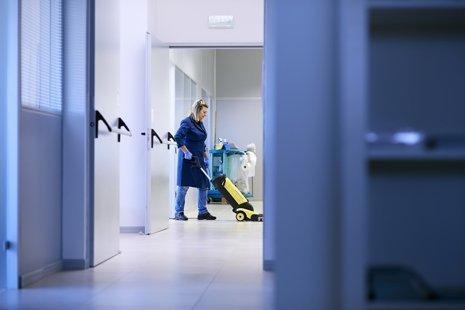 donna pulisce il pavimento di edificio industriale