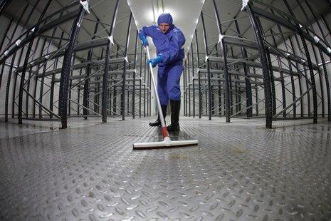 un operaio con divisa protettiva pulisce un magazzino vuoto