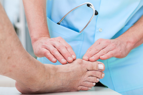 Experienced and licensed podiatrist checking toe of a patient in Fairport, NY
