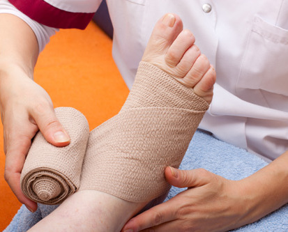 Foot pain specialist bandaging patient's foot in Fairport, NY