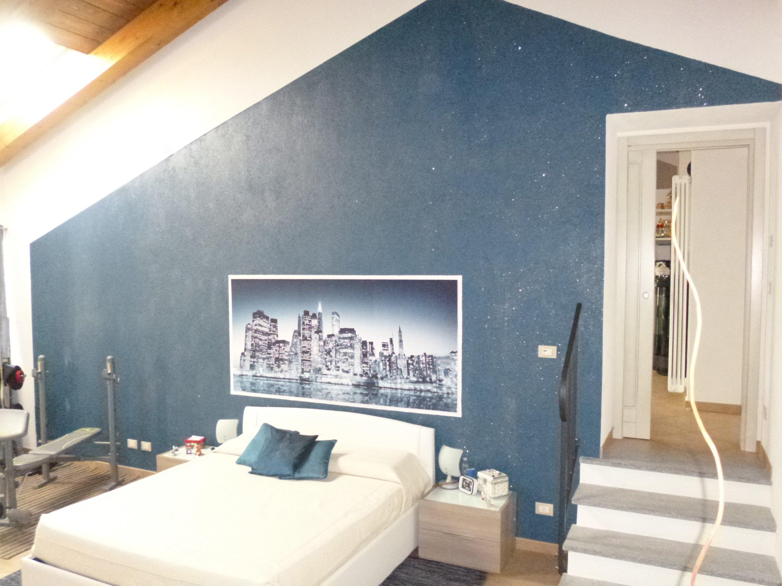 camera  da letto con parete blu e letto bianco
