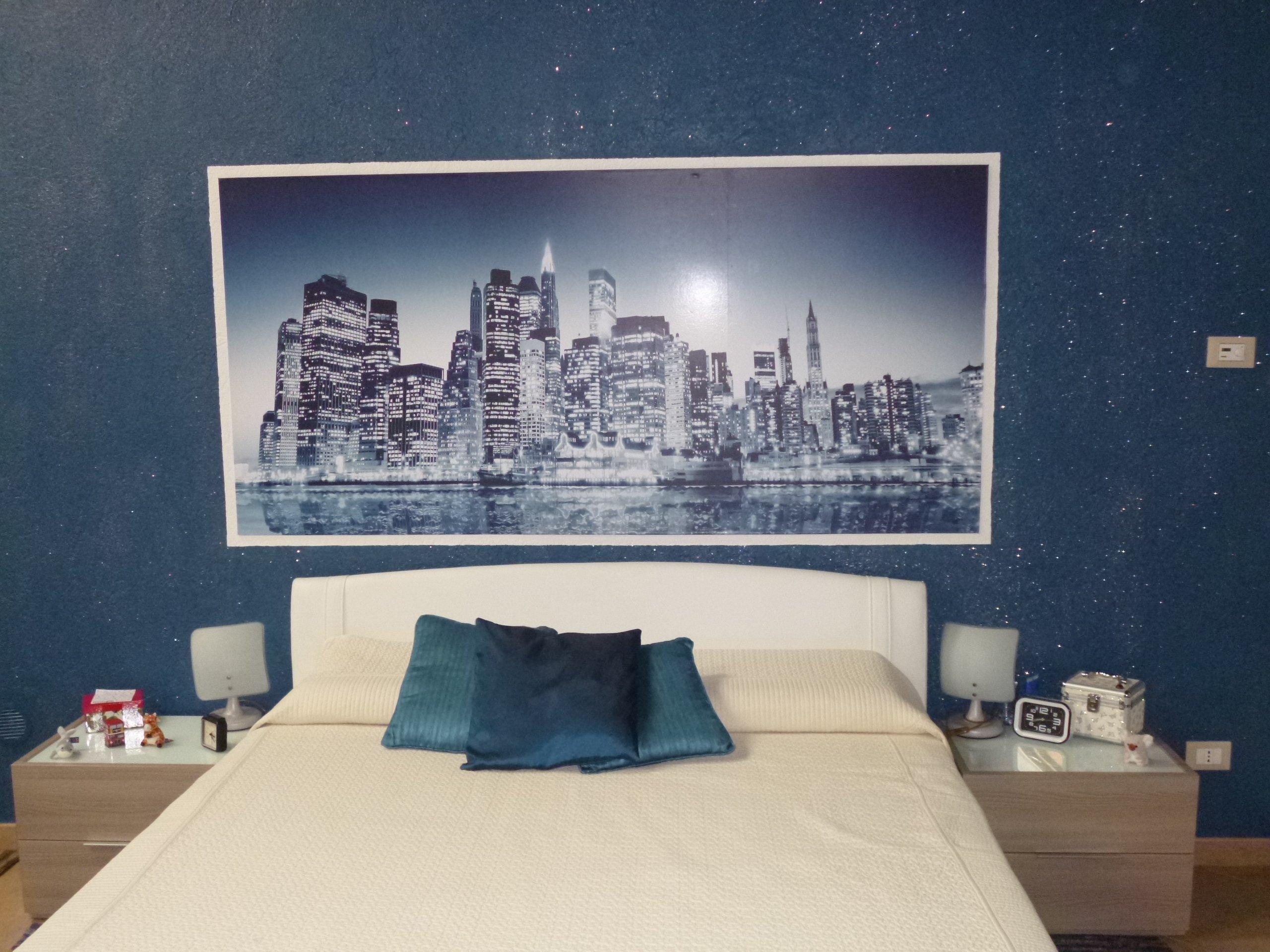 letto con lenzuola bianca e parete azzurro con un quadro