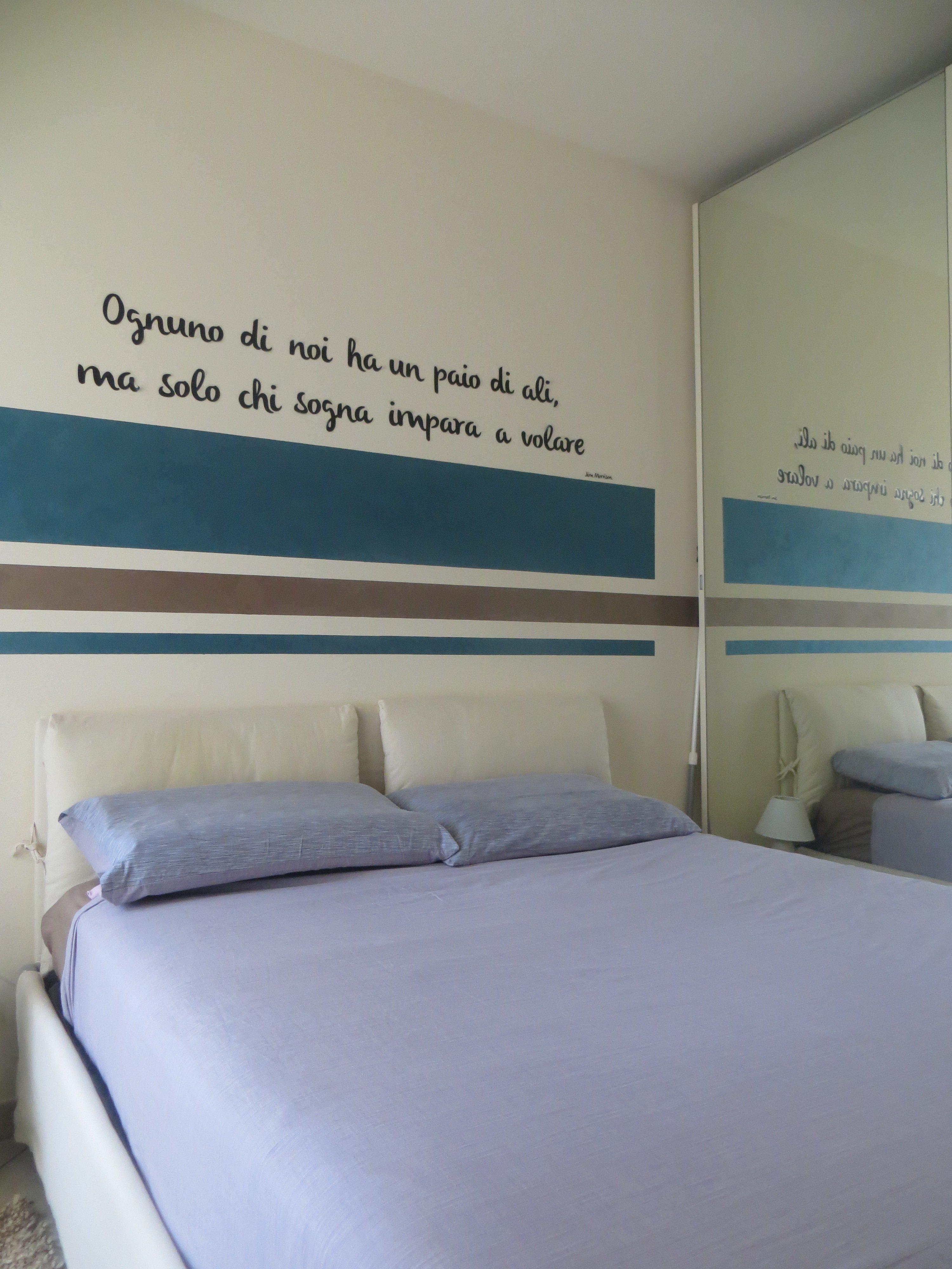 letto con lenzuola blu e una frase scritta sulla parete