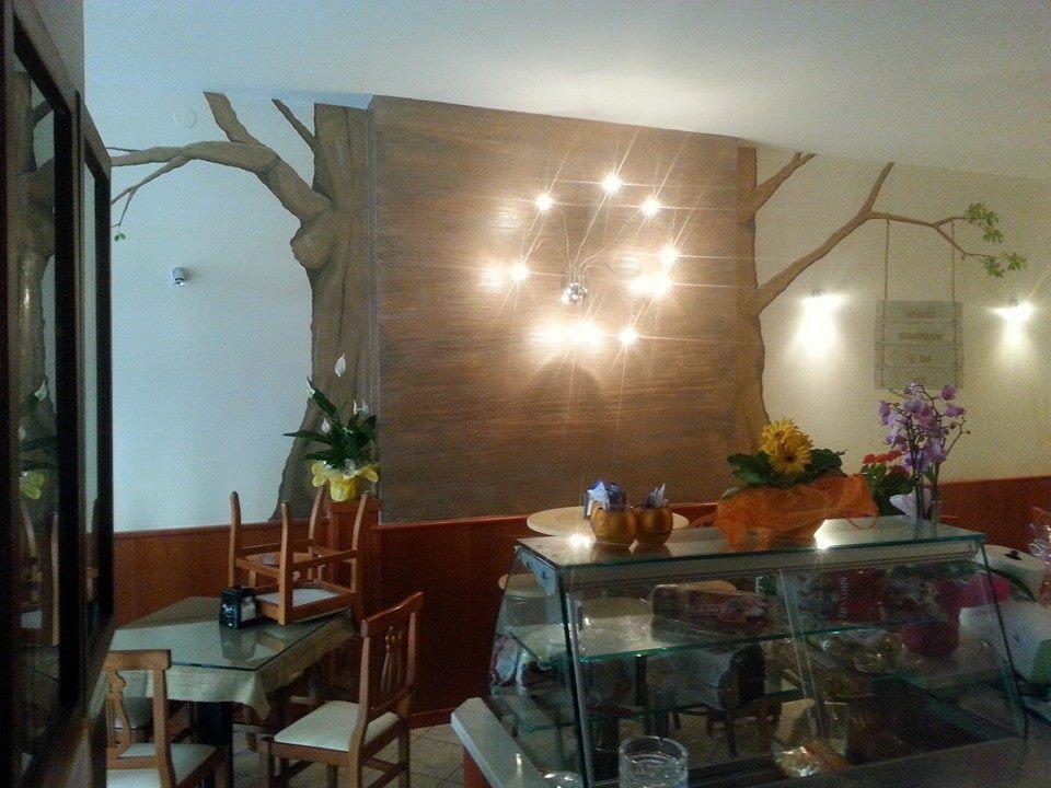 un bancone in vetro con prodotti alimentari accanto ad un tavolo con sedie