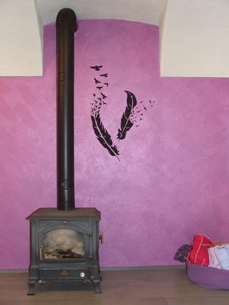 stufa con canna fumaria su muro rosa con due piume disegnate