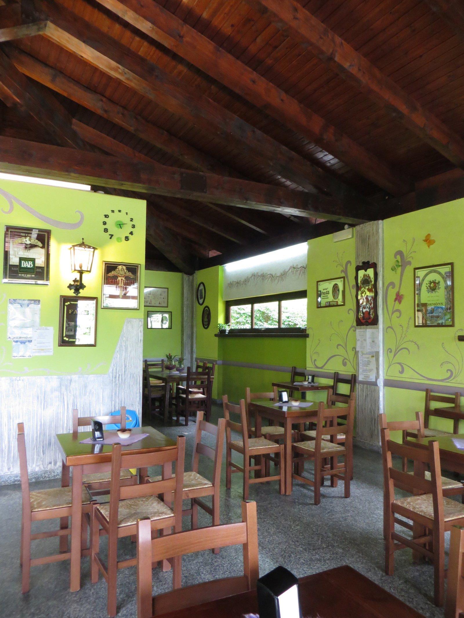 sala con tavoli e sedie e pareti verdi