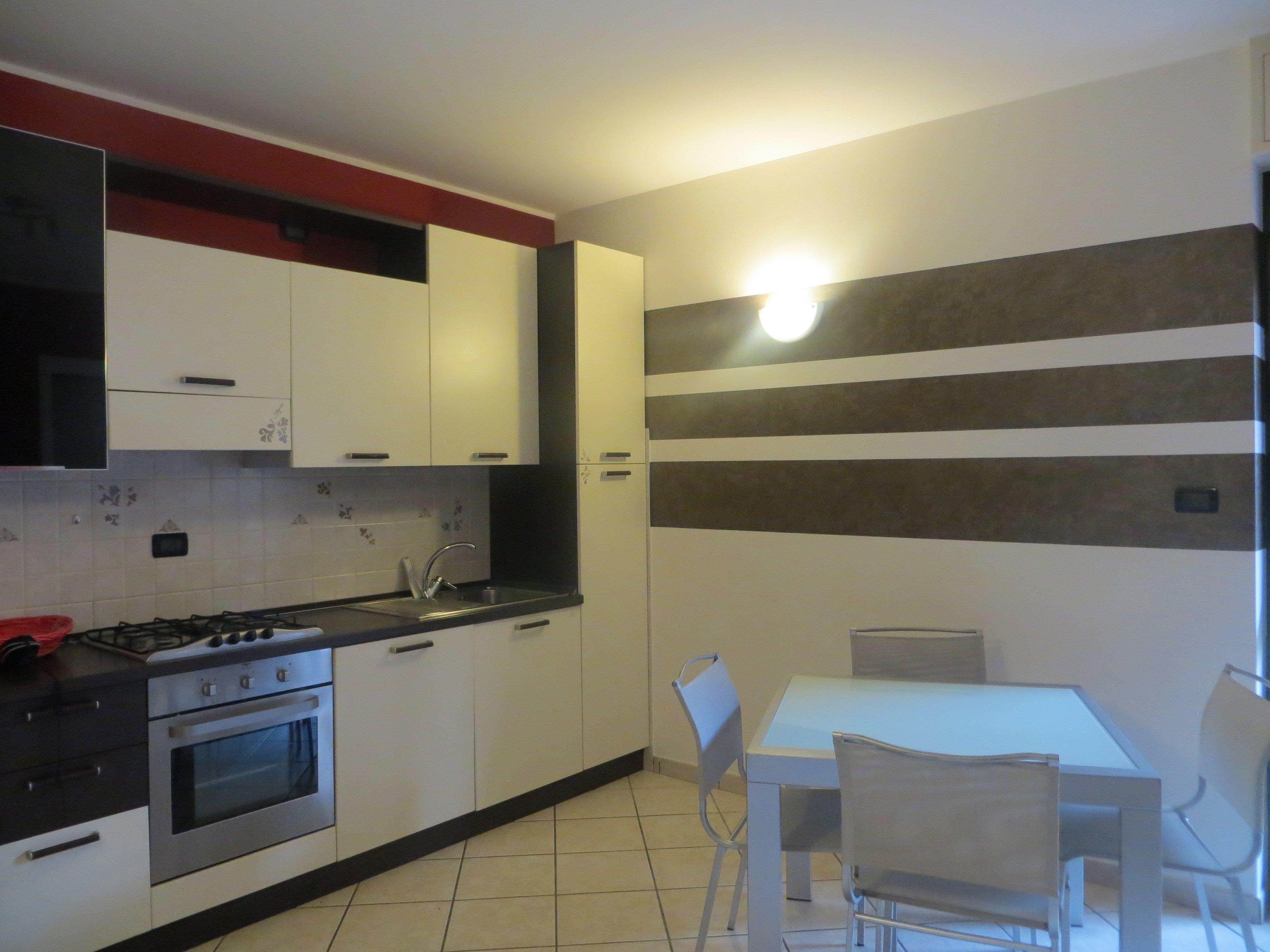 cucina di colore bianco con tavolo e sedie