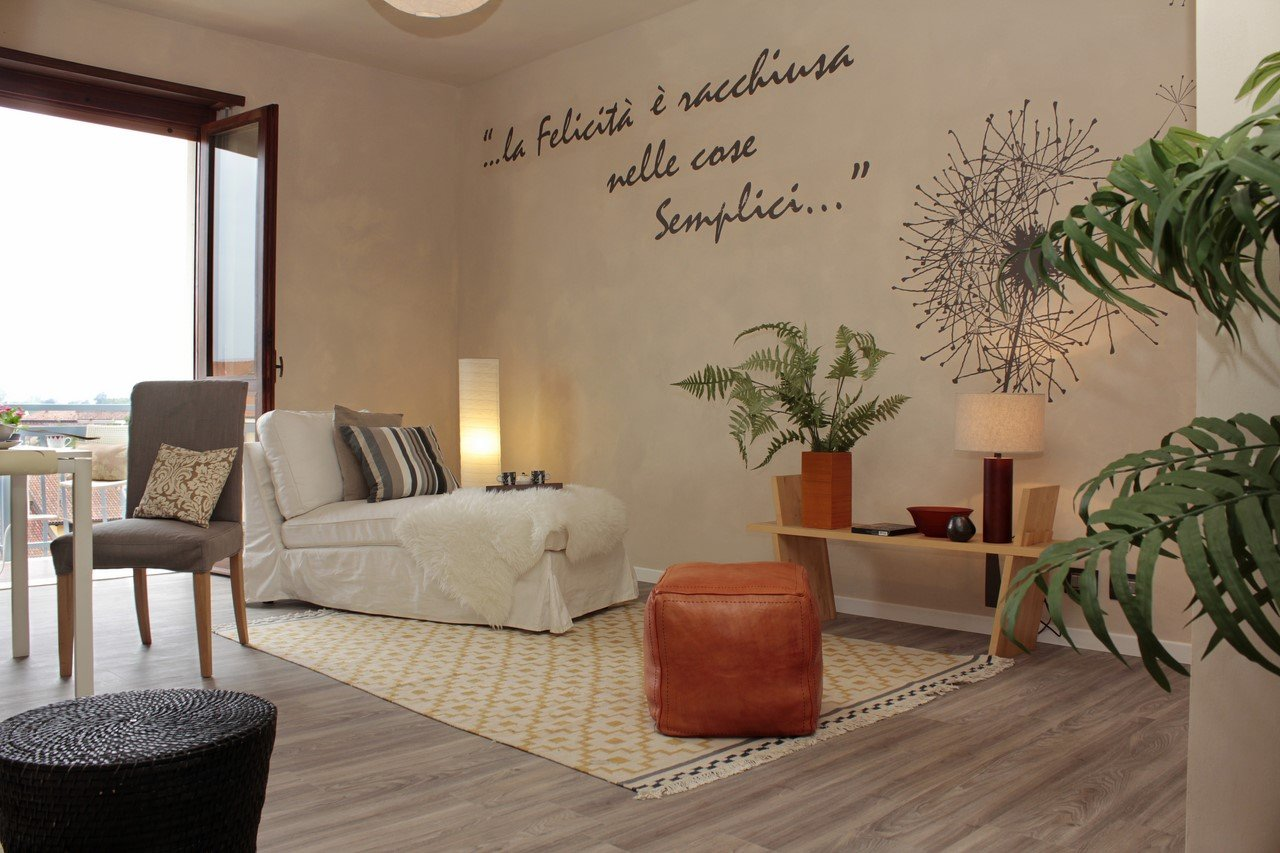 salotto con poltrona e sullo sfondo una frase scirtta sulla parete