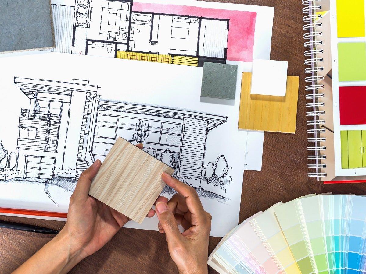 una mano tiene un pezzo di legno e sullo sfondo un disegno di una casa