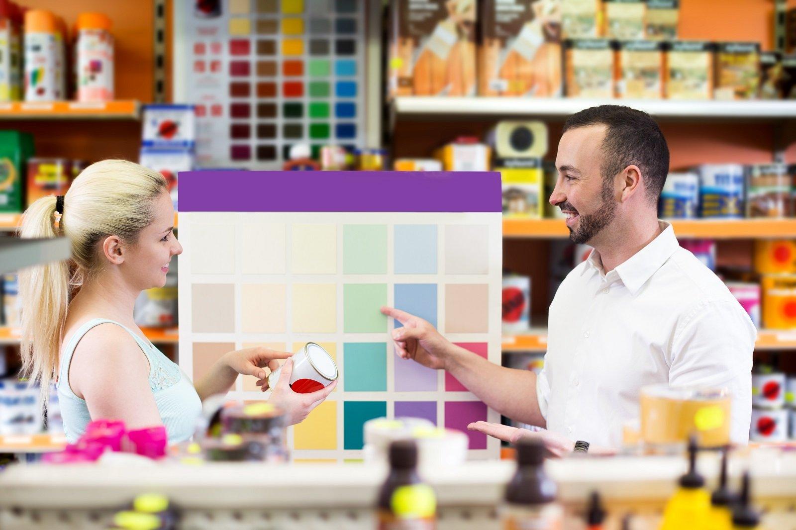 un addetto mostra colori di vernici esposte a una cliente