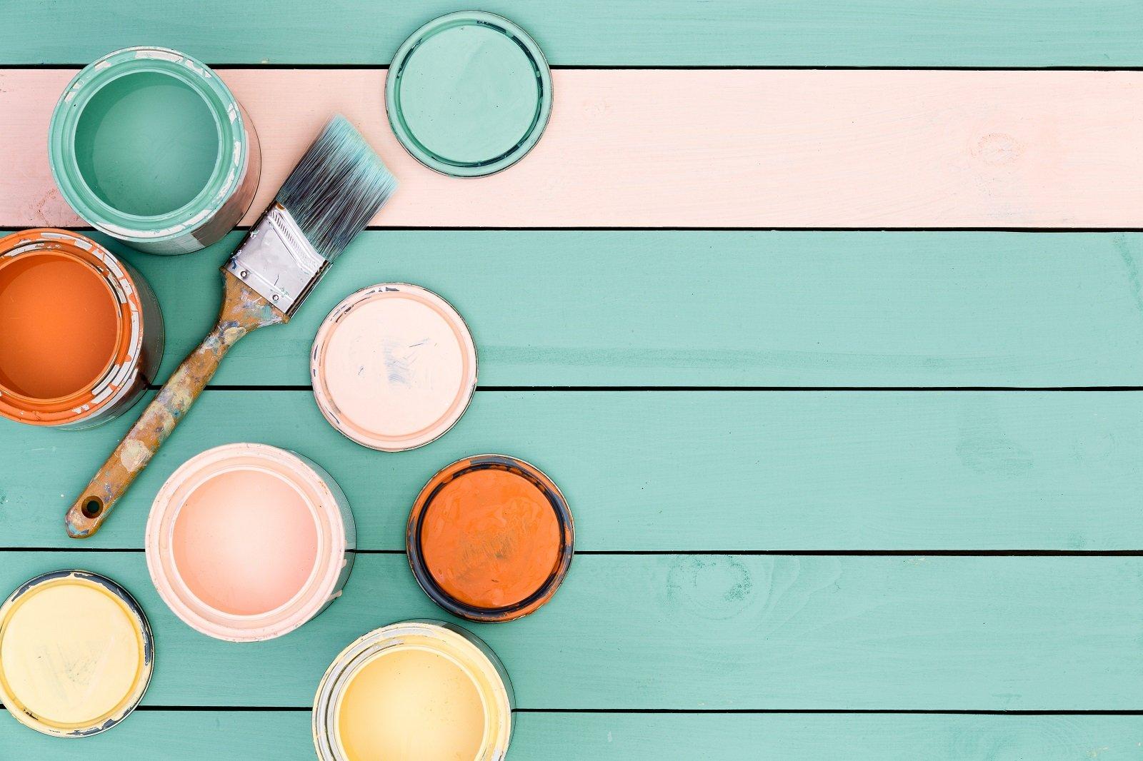 barattoli di vernice con pennello su un tavolo in legno azzurro