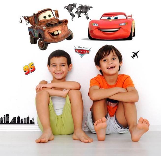 Bambini sorridenti seduti con alle spalle immagini di Cars