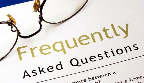 Paper saying Frequently Asked Questions and a pair of glasses