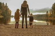 Mother holding hands with 2 children by a lake
