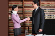 Woman in a neck brace shaking hands with man in a suit