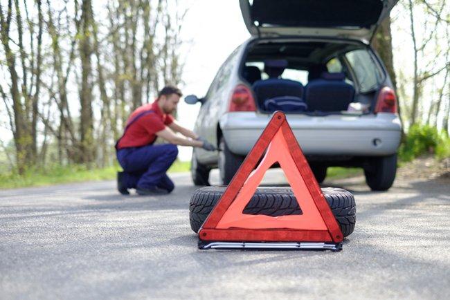 Un triangolo rosso d'emergenza poggiato sulla carreggiata e, sullo sfondo, un uomo che ripara uno pneumatico
