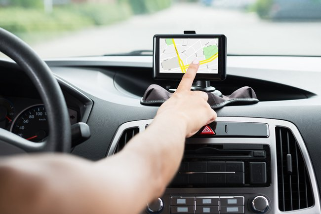 Una donna pigia il touch screen di un navigatore dentro l'auto