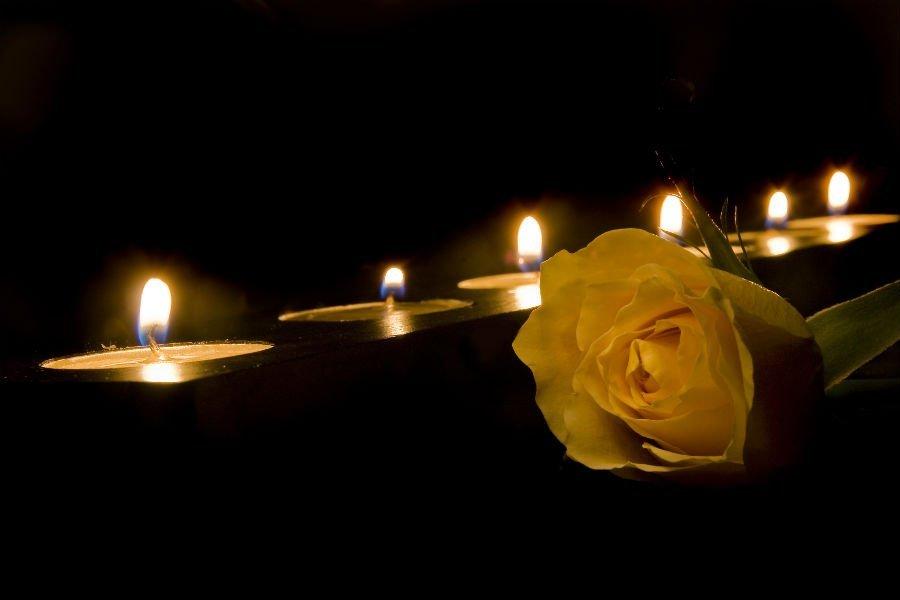 dei ceri accesi e una rosa bianca