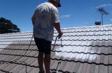 Man hoses tiled roof in Auckland