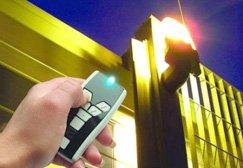 una mano con un telecomando che punta verso una luce di emergenza