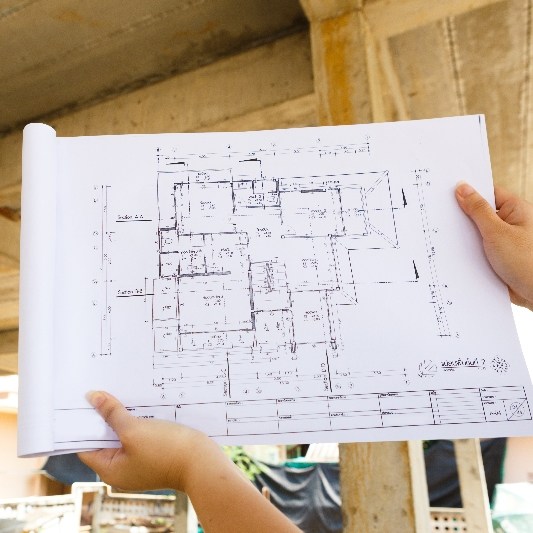 architect holding up floor plan to building