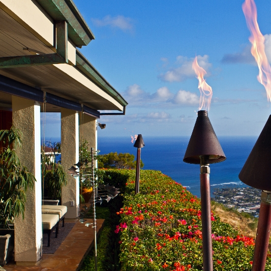 Honolulu house with burning tiki torches overlooking the ocean