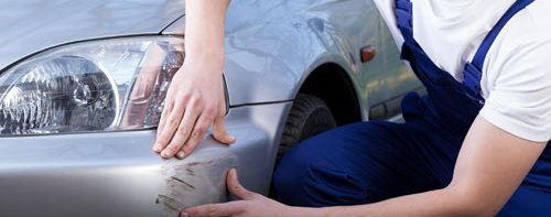 In quality auto body shop auto technician showing car dent in Groton, CT