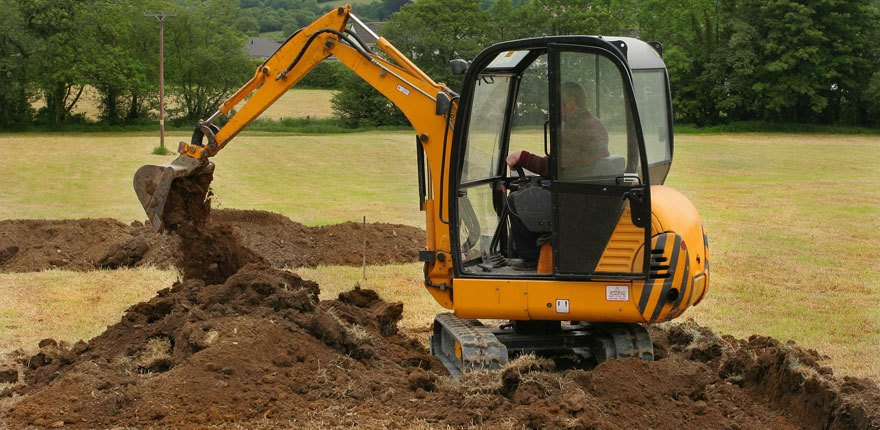 mini digger at work in a field