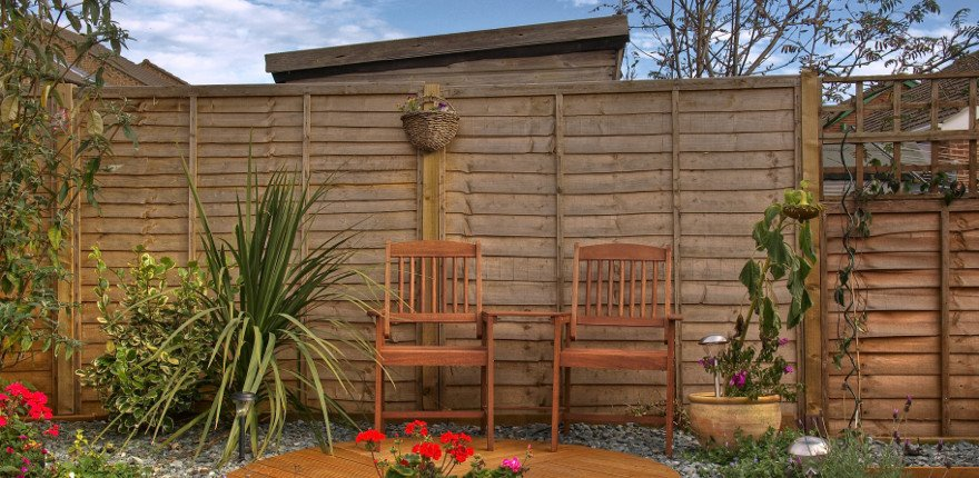 back garden area with larch lap fencing, wood furniture and pot plants