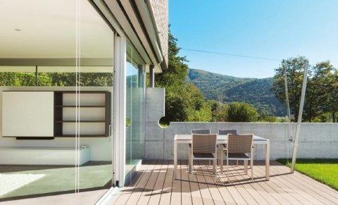 vista esterna di una casa con spazio aperto per mangiare, ante scorrevoli e giardino