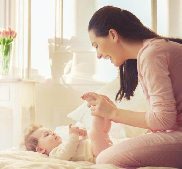 una donna mentre gioca con un bambino sul letto nella camera da letto