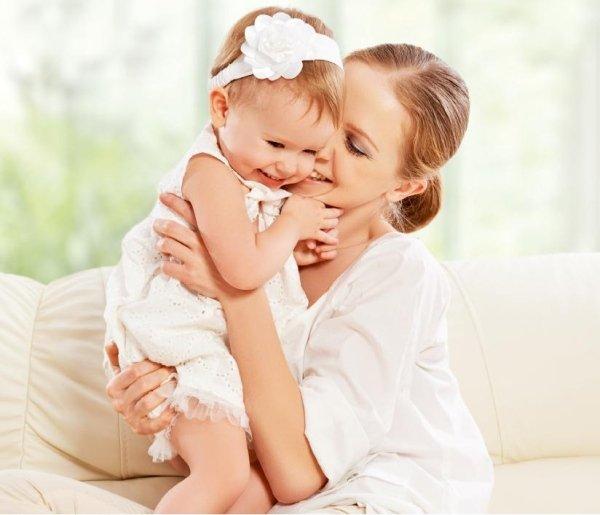 una donna mentre abbraccia e baci di una bambina