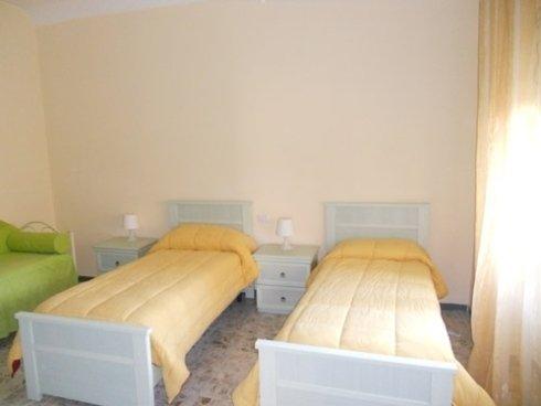 una stanza con tre letti, sulla sinistra uno con un piumone verde e in mezzo due con dei piumoni gialli e dei comodini con sopra delle lampade