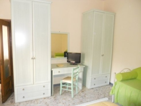 una stanza con vista di  due armadi bianchi ai lati, in mezzo una scrivania con una sedia e sopra un piccolo televisore nero