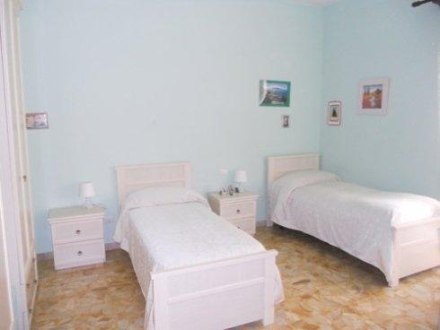 una camera da letto con muri azzurri con dei quadretti appesi, due letti singoli e due comodini con sopra delle lampade