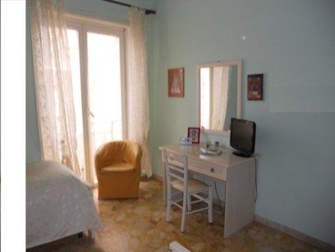 una stanza  con sulla sinistra un letto, una poltrona arancione e una scrivania con una sedia bianca e sopra un piccolo televisore nero