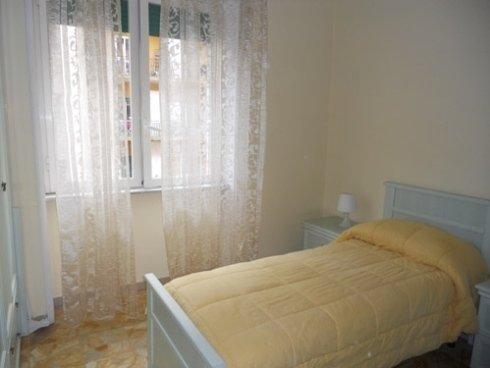 una camera con sulla destra un letto con un piumone giallo, una tenda trasparente e dietro la finestra