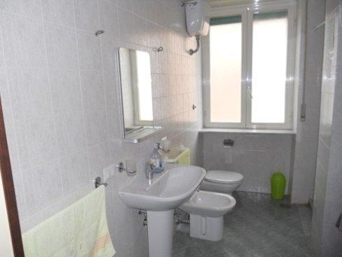 un bagno con sulla sinistra un lavabo bianco, un bidet, un wc e sopra uno scaldabagno