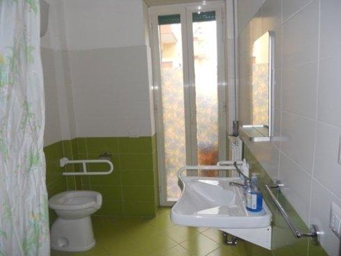 un bagno con pavimento con piastrelle verdi, sulla sinistra la tenda del box doccia, il wc e sulla destra il lavabo, una specchiera e in centro una finestra