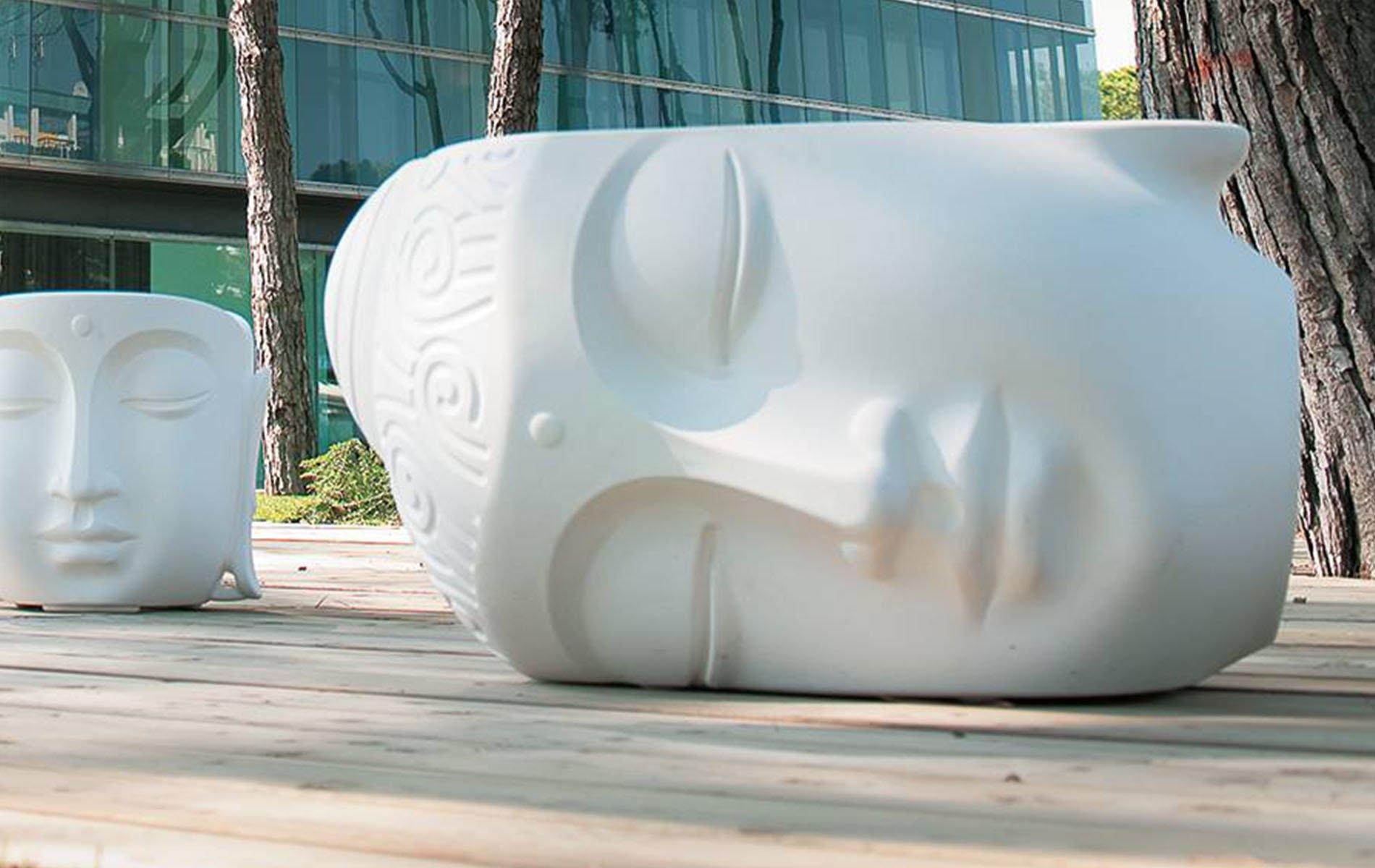 grandi statue di un viso all'interno di un giardino