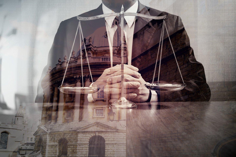 avvocato in ufficio con bilancia giustizia sul tavolo in legno