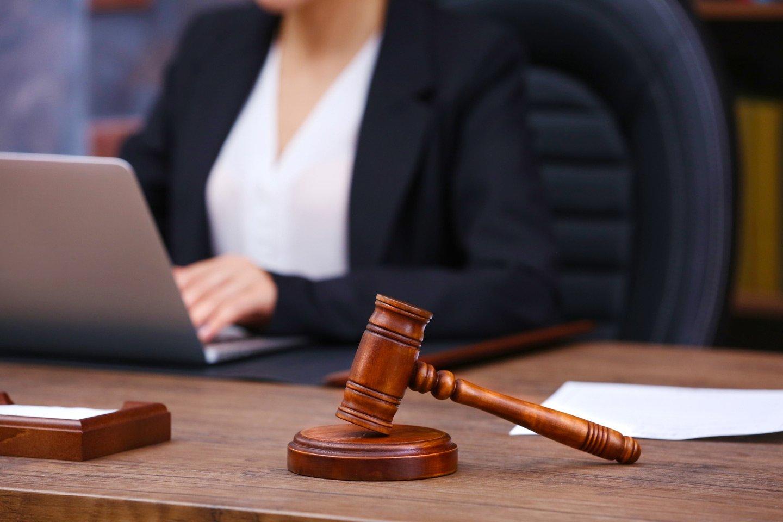 giudice martelletto sul tavolo di legno e avvocato femminile sullo sfondo