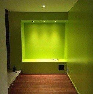 Corridoio con pareti verdi e al fondo, cornice verde con luci