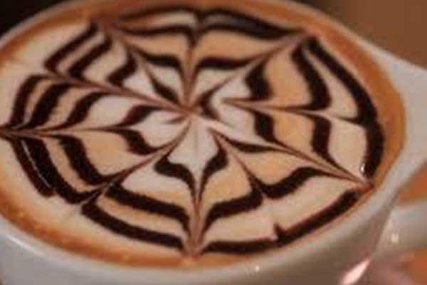 Bicchiere di latte macchiato e gocce di caffè a formare delle foglie