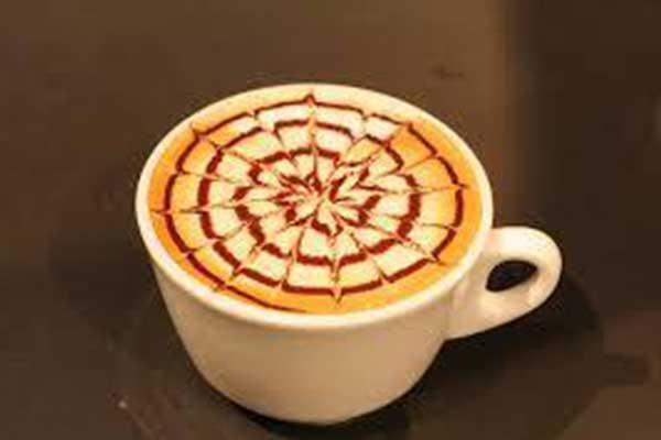 Una tazza di cappuccino con raffigurazione del sole e del mare con lo sciroppo al cioccolato