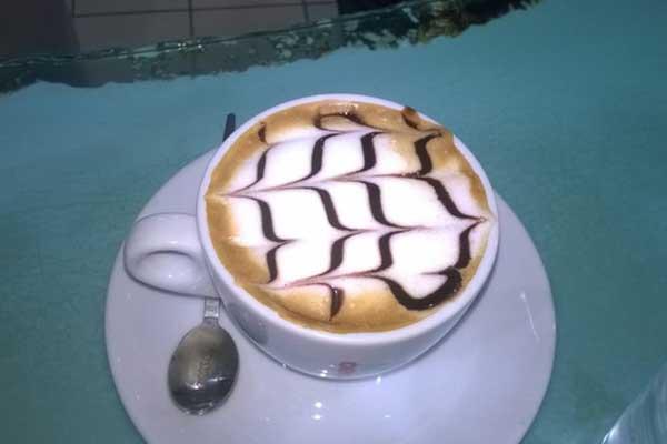 Vista ravvicinata di un cappuccino con disegni di sciroppo al cioccolato