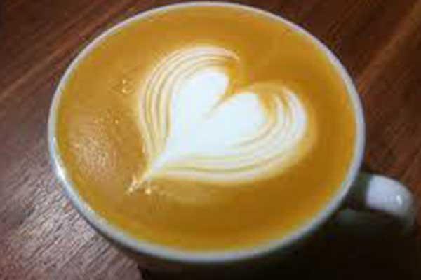 Una tazza di cappuccino con forma di cuore realizzato con la schiuma di latte