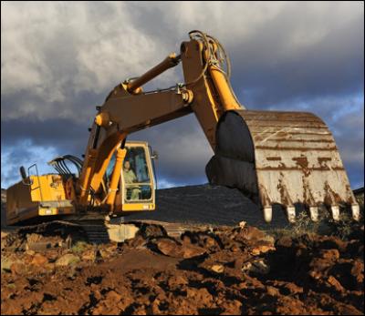 escavatice a lavoro in campo aperto con un cielo nuvoloso